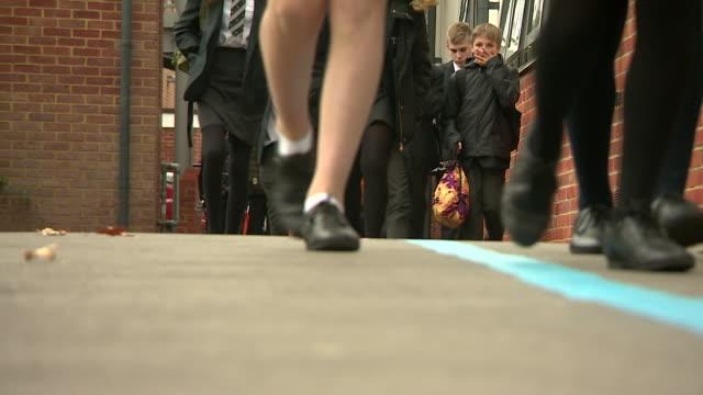 Anonymous schoolchildren walking out of school gates Sussex