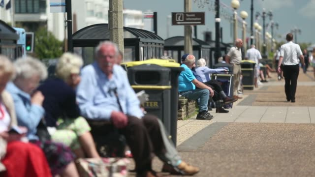 vídeos de stock, filmes e b-roll de anonymous shot of a group of people sitting on a wall along the seafront two with walking sticks in worthing uk on tuesday june 10 back view two... - soft focus