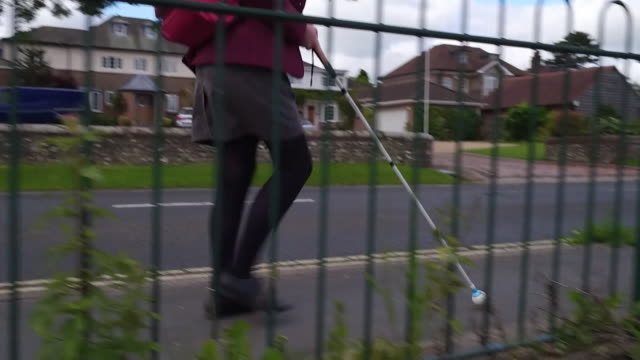 anonymous visually impaired schoolgirl walking to school with aid of a white stick cane hampshire - blindness stock videos & royalty-free footage