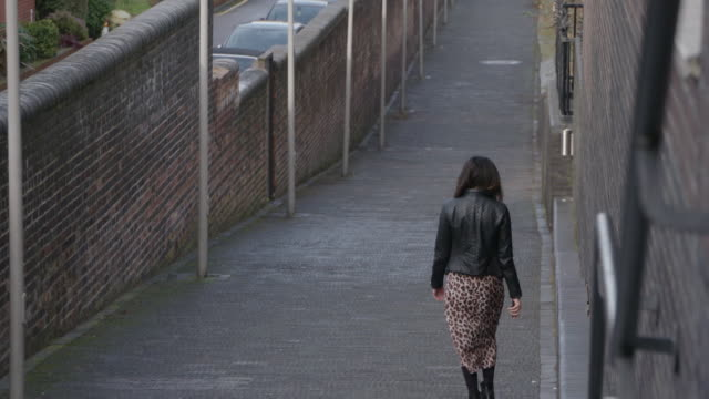 anonymous woman walking through alley away from camera - solitude stock videos & royalty-free footage
