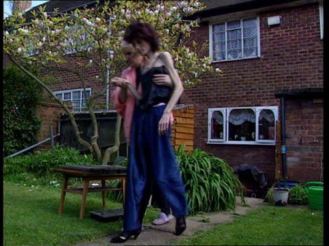 anorexia twins; england: birmingham: ext samantha kendall helped along thru garden by mother susie bv ditto as both sit down samantha pull out with... - anorexia nervosa stock videos & royalty-free footage