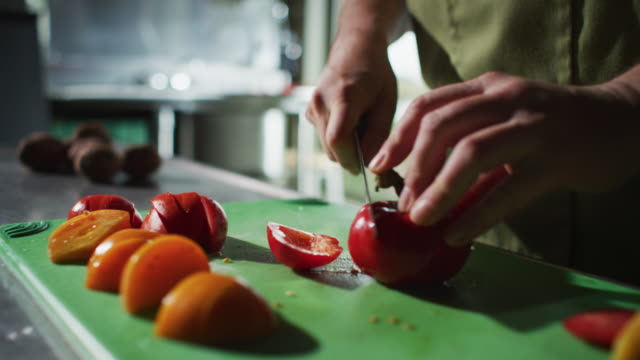 another red tomato is sliced on a cutting board during meal preparation at a farm-to-table restaurant. - farm to table stock videos & royalty-free footage