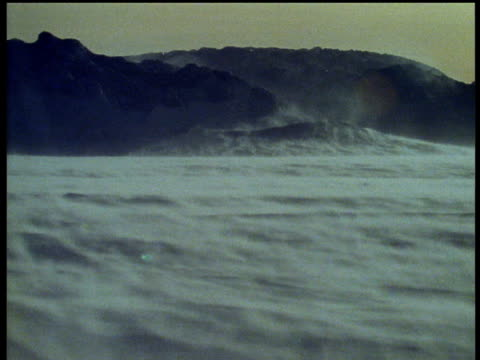 Antarctic ice cap, ice blows over surface in gale, rocks in background