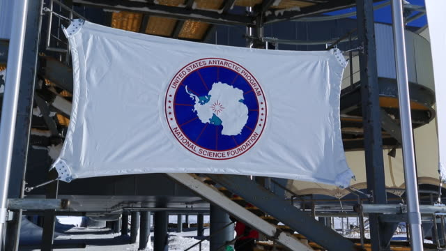 usa antarctic programme flag amundsen-scott south pole station, move to see scientists and tourists (unrecognizable) - pole stock videos and b-roll footage
