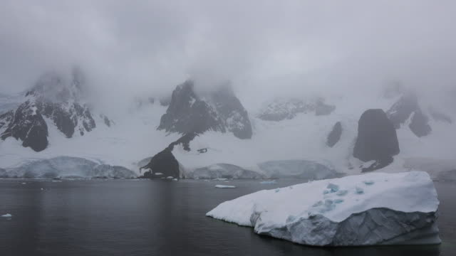 Antarctica a tracking shot past a floating iceberg on a foggy day