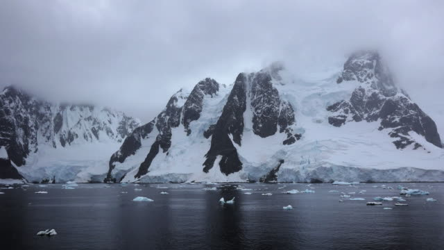 Antarctica rocks snow and reflections along the Lemaire Channel