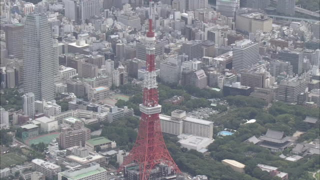 A TV antenna tops the Tokyo Tower and looms above the Zojoji Temple.