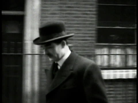 anthony eden in coat hat briefcase walking away from number 10 downing street door tracking eden walking by on street unidentified man taking... - downing street stock-videos und b-roll-filmmaterial