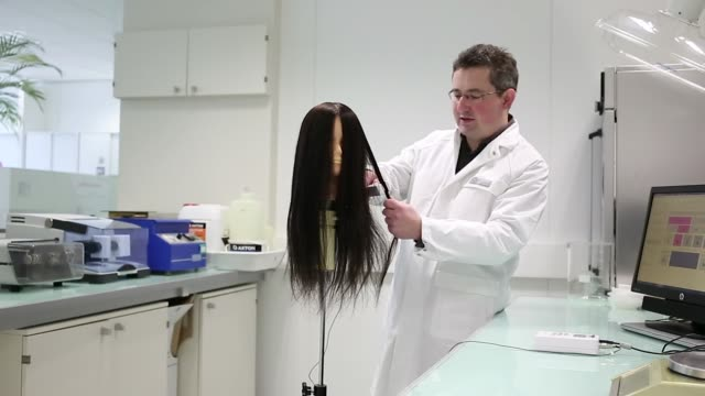 anthony galliano international instrumental science manager at l'oreal sa uses silicone sound frequency hair tongs on a mannequin head which... - serving utensil stock videos and b-roll footage
