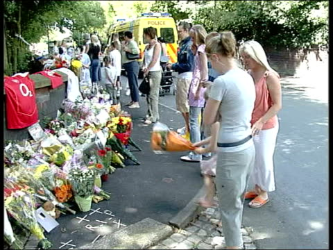 suspects arrive back in uk england liverpool huyton ls crowd gathered to look at floral tributes at scene of murder side ls young girl adds bouquet... - composizione di fiori video stock e b–roll