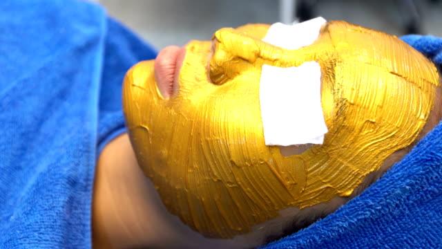 vídeos de stock, filmes e b-roll de antienvelhecimento facial com massagem creme máscara dourado - anti higiênico