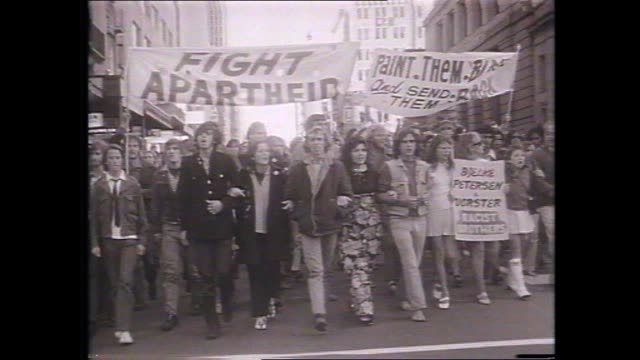 vídeos de stock, filmes e b-roll de anti apartheid springbok rugby tour demonstration march in brisbane marchers and banners fight apartheid paint them black and send them back bjelke... - marchando