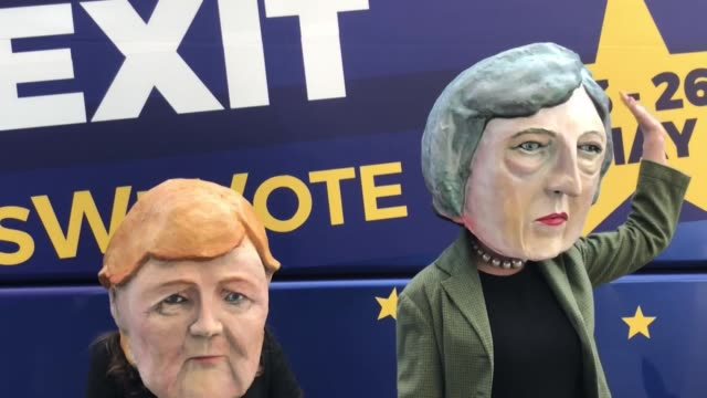 Anti Brexit protest outside EU in Brussels people wearing giant heads of Theresa May and Angela Merkel