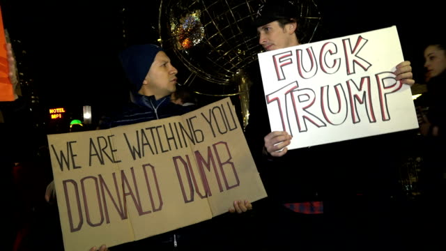 anti donald trump protesters gather in front of the trump international hotel tower in new york city ahead of the us presidentelect's presidential... - amtseinführung stock-videos und b-roll-filmmaterial
