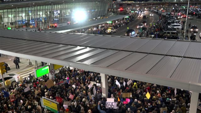 anti - donald trump protesters gathered in jfk in the borough of queens, new york city to protest the controversial executive order signed by... - kennedy airport stock videos & royalty-free footage