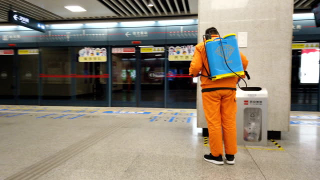 anti epidemic personnel are spraying disinfectant in metro station during the coronavirus outbreak,xi'an,china. - schutz und arbeitskleidung stock-videos und b-roll-filmmaterial