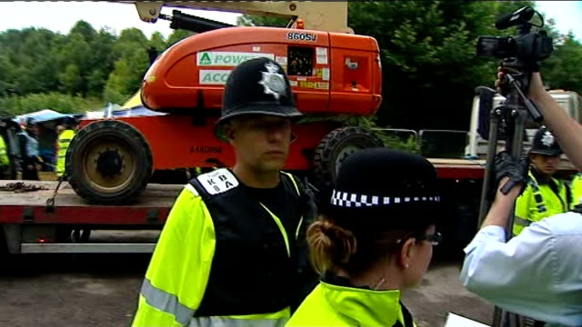 vídeos y material grabado en eventos de stock de anti fracking protests continue in sussex protester led away by police truck along past police officers and entering site police along moving... - placard