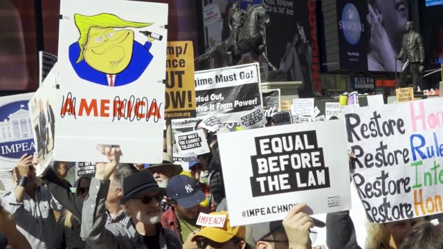 anti president donald trump activist rallied at midtown manhattan's duffy square in times square demanding that congress impeach the president - united states congress video stock e b–roll