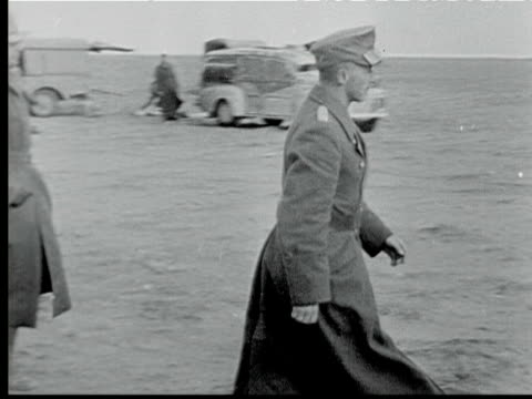 vídeos de stock, filmes e b-roll de antiaircraft gun w/ white surrender flag nazi general walks across field saluting surrenders to british officer troops marching past burning area... - oficial posto militar