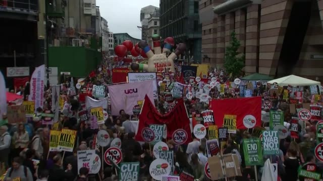 london ext antiausterity protesters in march with placards and banners within city of london - itv weekend lunchtime news点の映像素材/bロール