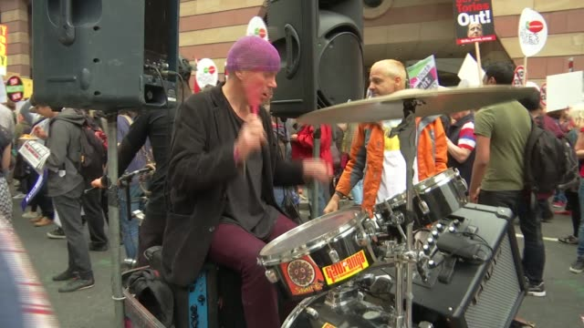 antiausterity march in london man playing the drums as man plays guitar next - itv london tonight weekend点の映像素材/bロール