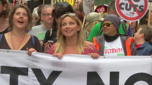 vídeos y material grabado en eventos de stock de antiausterity march in london man wearing black v for vendetta mask singer charlotte church at the head of the march protesters standing on wall... - placard