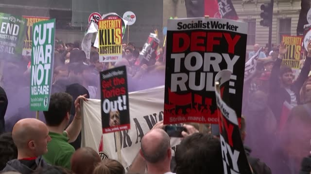 anti-austerity march in london; police officers in line in front of downing street gates demonstrators with red smoke from smoke bomb rising people... - charlotte church stock videos & royalty-free footage
