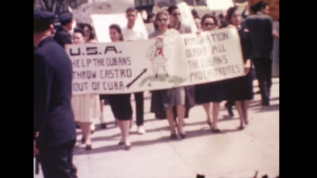 AntiCastro march on the White House around the time of the Bay of Pigs invasion demonstrators carrying signs with police observing protesters with...