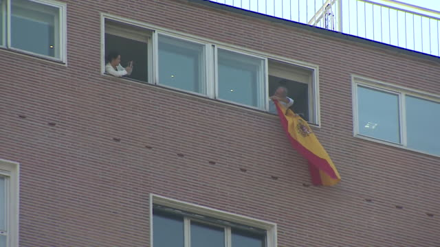 AntiCatalonia independence demonstrators displaying Spanish flags and a banner outside an office building on the eve of Fiesta Nacional de Espana