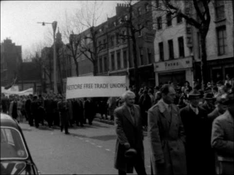 anticommunist demonstrations in london england london whitehall ext people marching towards up road / men carrying banner reading free poles / men... - communism stock videos & royalty-free footage