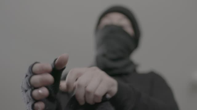 antifa member puts on glove in slow motion - anti fascism stock videos & royalty-free footage