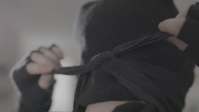 antifa members ties mask around head, slow motion close-up - anti fascism stock videos & royalty-free footage