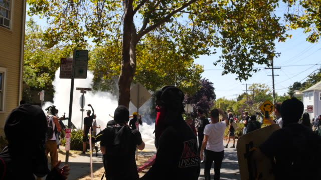 antifa protesters run after berkeley police throw smoke grenades and shoot a rubber bullet at a crowd to break up a fight protesters had followed... - anti fascism stock videos & royalty-free footage