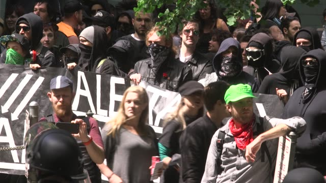 antifa wearing black bandana masks protest at portland free speech rally - オレゴン州 ポートランド点の映像素材/bロール