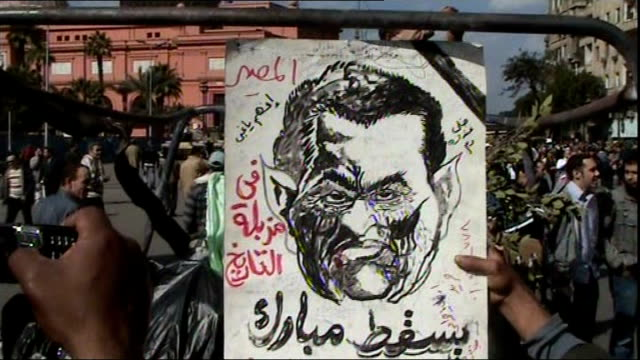 vidéos et rushes de anti-government protesters call for general strike as they continue to defy curfew; egypt: cairo: ext anti-government protester holding up satirical... - satire