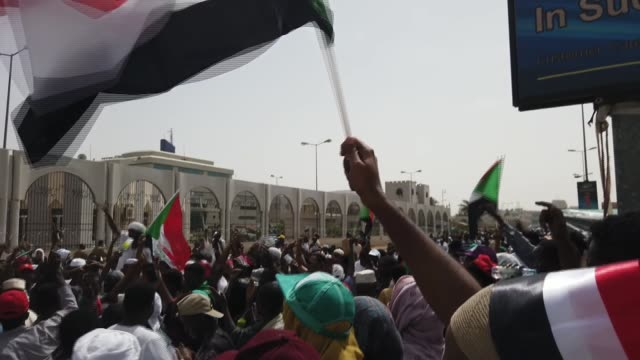 Antigovernment protesters demand recognition of women's rights SUDAN Khartoum EXT Sudanese flag waved in air Demonstrators chanting as along Vox pop