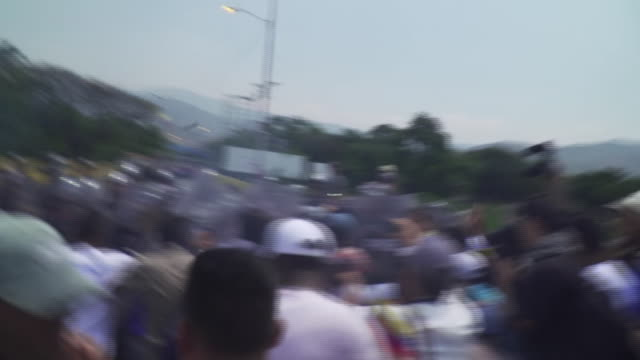 antigovernment protesters on the venezuelacolombia border being attacked with tear gas and rubber bullets by venezuelan government troops - bombola video stock e b–roll