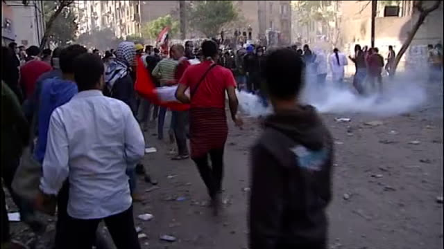 AntiGovernment protesters surge through streets of Cairo PAN as teargas cannister flies through the air and lands among the crowd one protester picks...