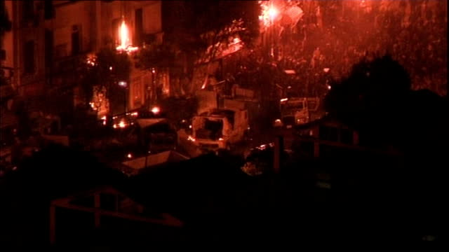 clashes between protesters and Mubarak supporters EXT Barricades lit up by flares and sound of gunfire heard in background SOT Burning vehicle being...