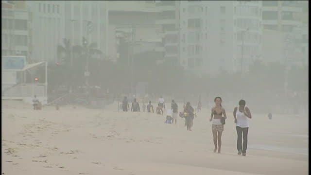 stockvideo's en b-roll-footage met antigovernment protests continue despite president's pledge brazil rio de janeiro ipanema ext people on beach on overcast day including two women... - jogster