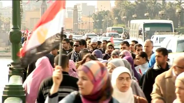 Cairo EXT Protesters along including woman carrying Egyptian flag 'Facebook' grafitti written on shutter as people walk past Various of demonstrators...