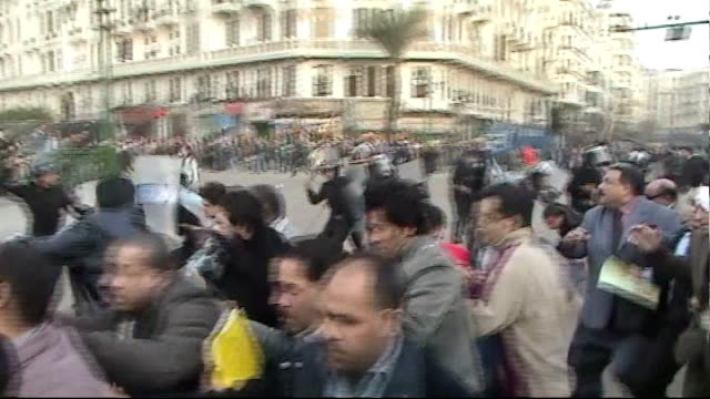 vídeos de stock, filmes e b-roll de antigovernment protests continue on streets protesters being chased by riot police outside court buildings and police beating others on road - arab spring