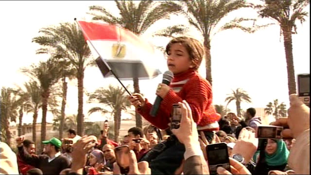 President Mubarak makes television address Child on shoulders of her father leading chants as people take photographs with their mobile phones SOT...