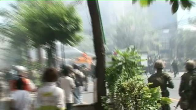 troops take control Long Shot Firefighters spraying water on burning bus ZOOM IN