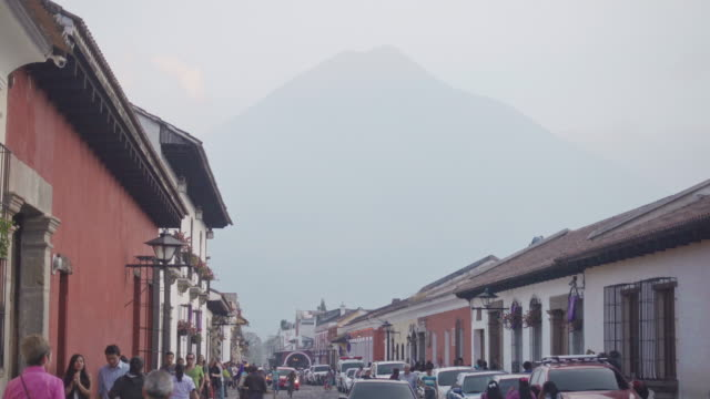 antigua guatemala colonial street with people, cars and a volcano on the background - 四旬節点の映像素材/bロール