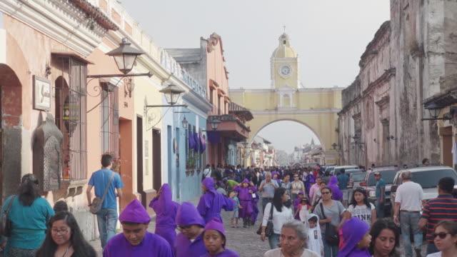 antigua guatemala famous street during lent / easter catholic celebration. people dressed in purple costume crossing santa catalina arch. - 四旬節点の映像素材/bロール