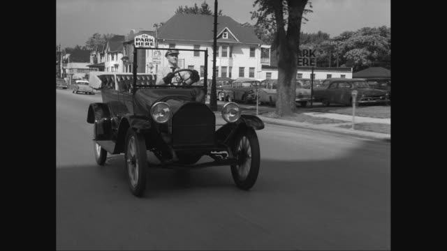 WS TS Antique car moving on street / United States