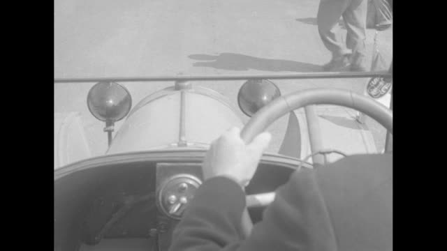 Antique car with large windshield slowly rolls past crowd / gloved hand squeezes bulb of spiral horn / PAN vintage car driving past / cars with two...