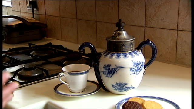 antique gadget collector wins award; collins & reporter chatting as pouring cup of tea with special non-drip teapot sot reporter raising cup to lips... - ヒトの口点の映像素材/bロール