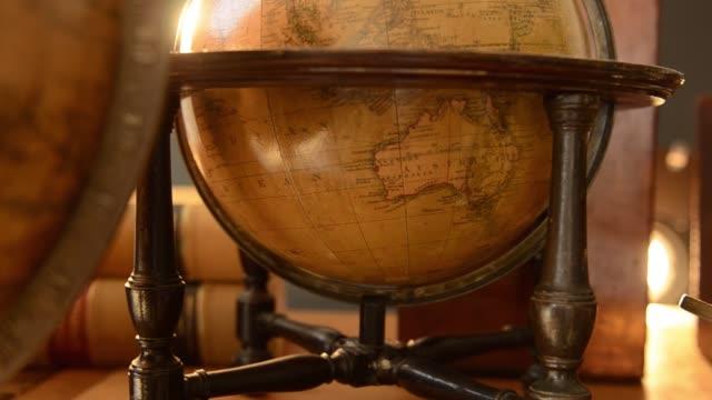 antique globes and microscope on table - gruppo medio di oggetti video stock e b–roll